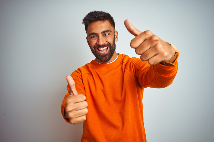 Young man wearing orange sweater over isolated white background approving doing positive gesture with hand, thumbs up smiling and happy for success. Winner gesture.