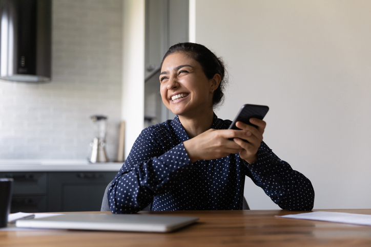 Overjoyed young indian woman holding cellphone laughing on internet joke.