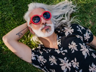 Mature gray hair man lying on grass in shade with sunglasses on. Puerto Madero, Buenos Aires, Argentina.