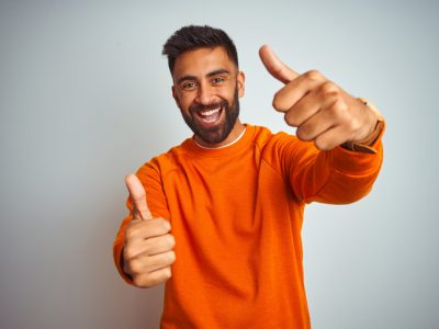 Young indian man wearing orange sweater over isolated white background approving doing positive gesture with hand, thumbs up smiling and happy for success. Winner gesture.